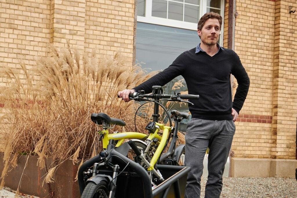 Thomas zeigt das mit seinem Faltrad beladene Lastenvelo